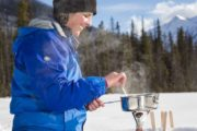 Your guide will make maple taffy in the snow on a snowshoeing tour with Discover Banff Tours