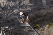 Climb a rock wall on Mount Norquay's Via Ferrata Skyline Route in Banff in the Canadian Rockies