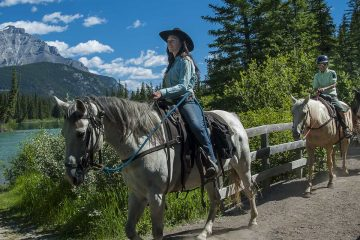 Follow your guide along the Bow River on a horseback ride with Discover Banff Tours in the Canadian Rockies