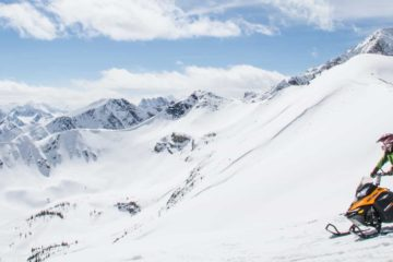 Ride a snowmobile in an open powder bowl in the Canadian Rockies