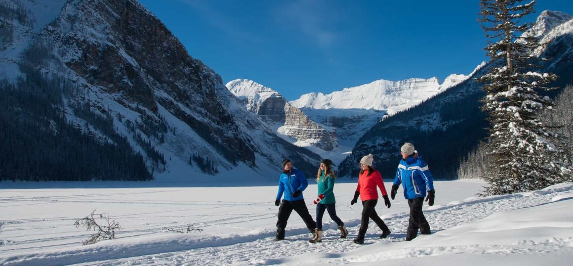 Stroll along the frozen lake shoreline with your guide on the Discover Lake Louise winter tour with Discover Banff Tours in the Canadian Rockies